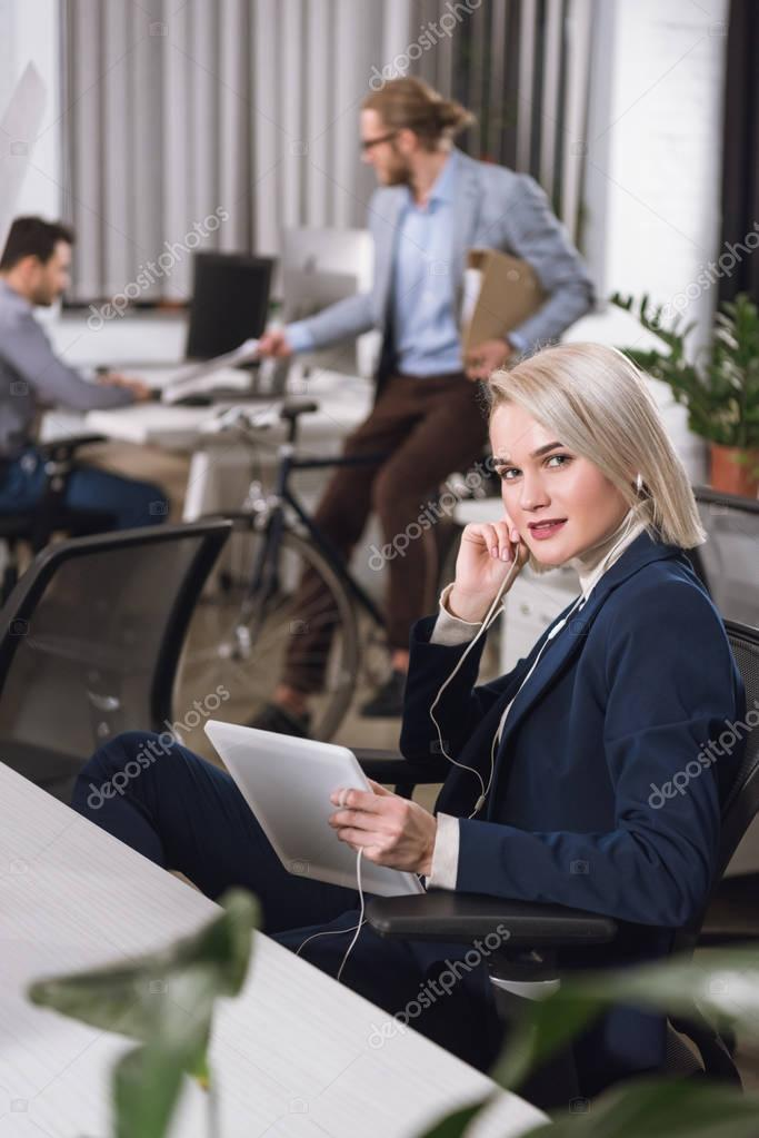 businesswoman in earphones with tablet