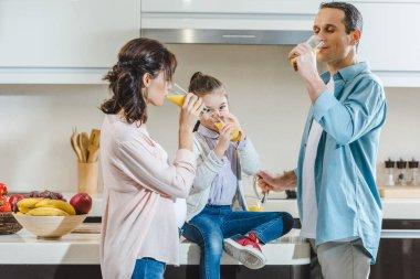 happy family drinking juice at kitchen