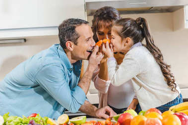 happy family beside table with fruits and vegetables applies little carrots to noses and looking at each other at kitchen
