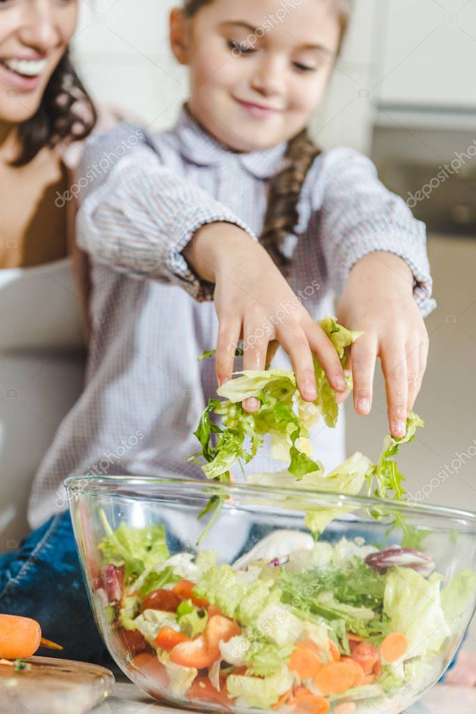 mother with daughter making salad
