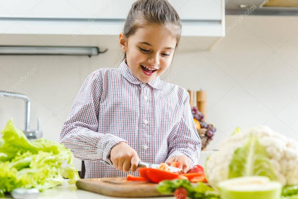 kid slicing pepper on chopping board