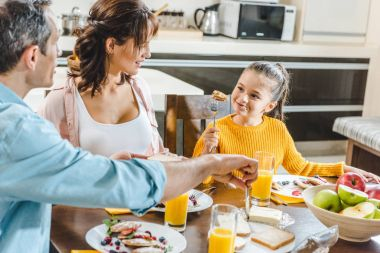 happy family eating pancakes at table with juice and fruits at kitchen