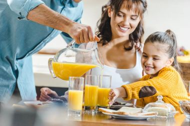 happy family at table, man pouring juice in glasses to woman and kid at kitchen