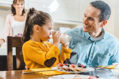 happy family at kitchen, daughter with father sitting at table with pancakes and looking at each other when daughter drinking milk