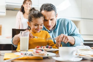 cheerful family together eating pancakes with berries at table on kitchen