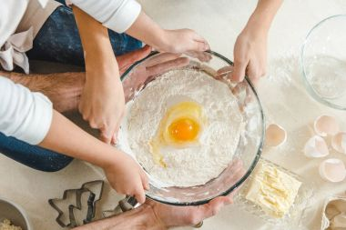 hands holding flour with egg in bowl