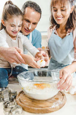 cropped image of happy family splitting egg in bowl at kitchen