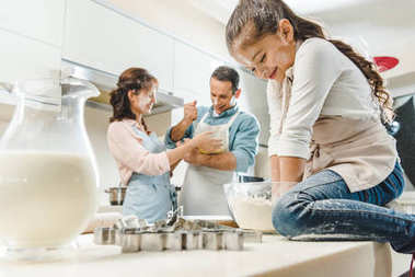 happy caucasian family in flour making dough at kitchen