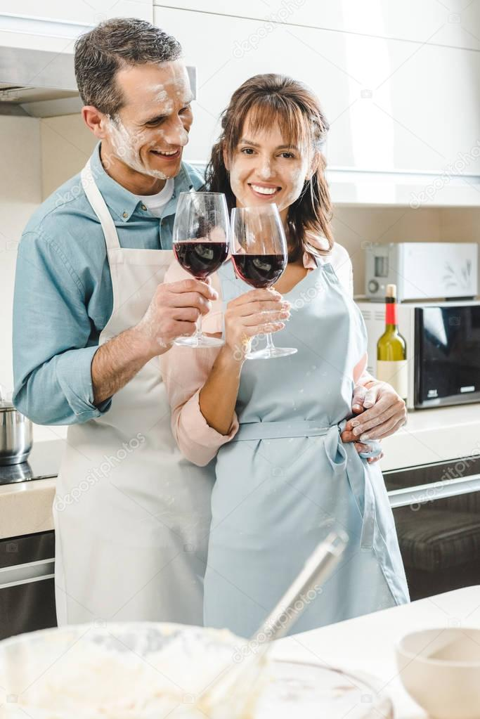 couple with wine at kitchen