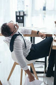 Photo tired young businessman sleeping on chair at office workplace