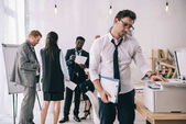 fiatal jóképű üzletember Copierrel irodában homályos munkatársaival, a háttér