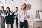 mladá manažerka s bolestí hlavy, čekání u kopírky v kanceláři