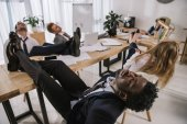 Photo exhausted businesspeople sleeping in conference hall with feet on table