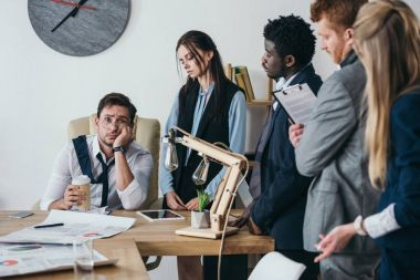 group of young managers talking to overworked boss