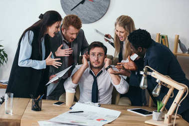 businessman having trouble with deadline and covering ears while colleagues shouting at him