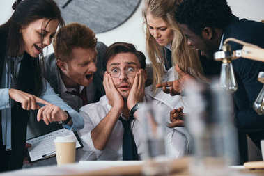 businessman having trouble with deadline while colleagues shouting at him