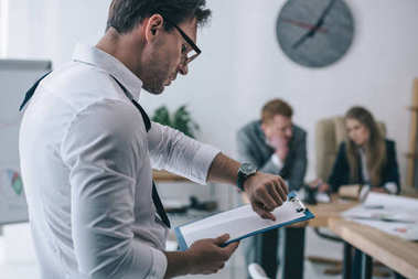 untidy overworked businessman checking time with watch at office