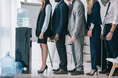 side view of managers standing in queue for water dispenser