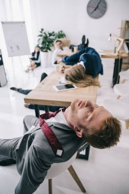 overworked business colleagues sleeping at office