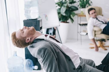 exhausted businessman sleeping on chair at messy office