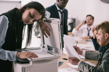 exhausted zombie like businesswoman sleeping on copier at office