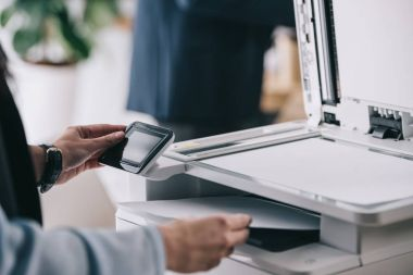 cropped shot of woman in formal wear using modern copier