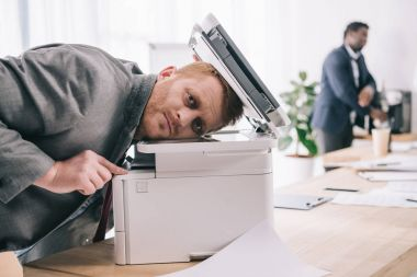 overworked young businessman leaning on copier at office