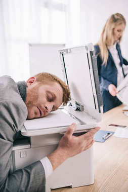 overworked young businessman sleeping with head on copier at office