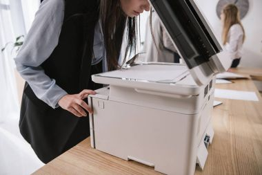 exhausted young businesswoman sleepy leaning on copier at conference room