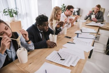 businesspeople eating noodles together at office while having conversation