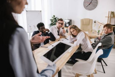 overworked businesspeople sitting at conference hall and listening to colleague with tablet at office
