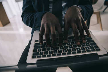 cropped shot of african american businessman working with laptop