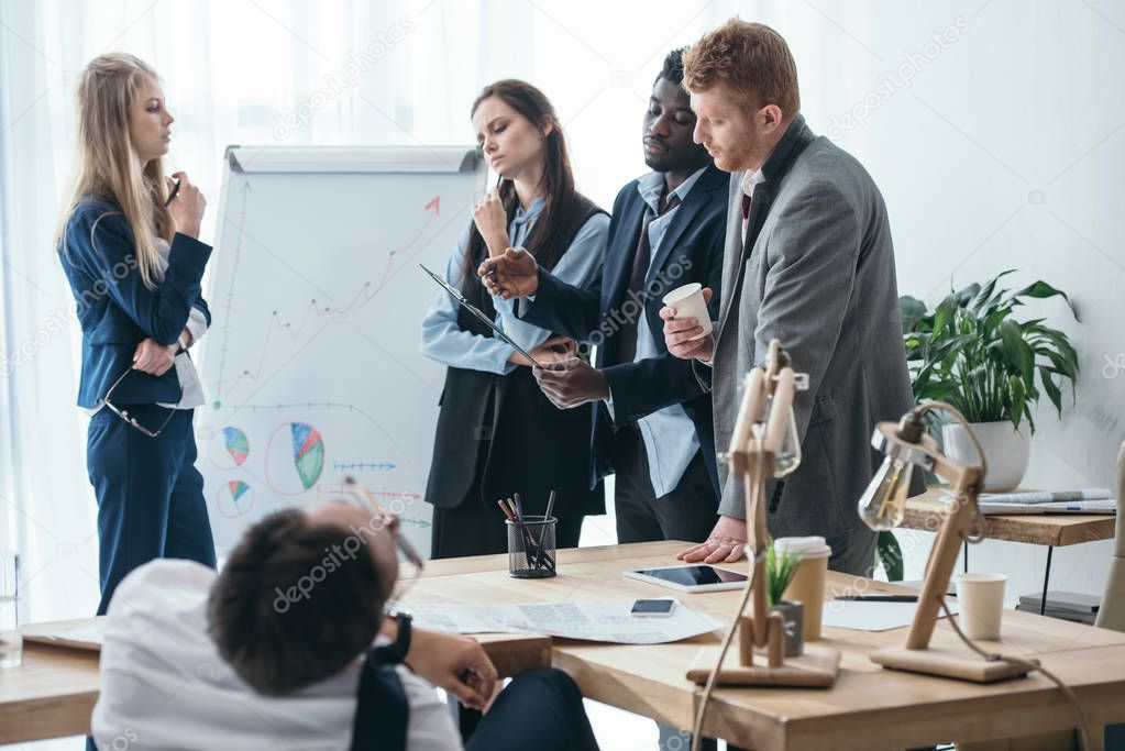 group of overworked managers having conversation at office