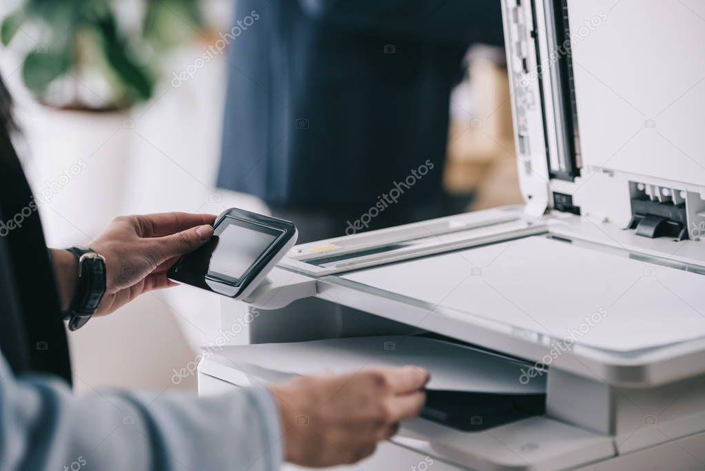 cropped shot of woman in formal wear using modern copier