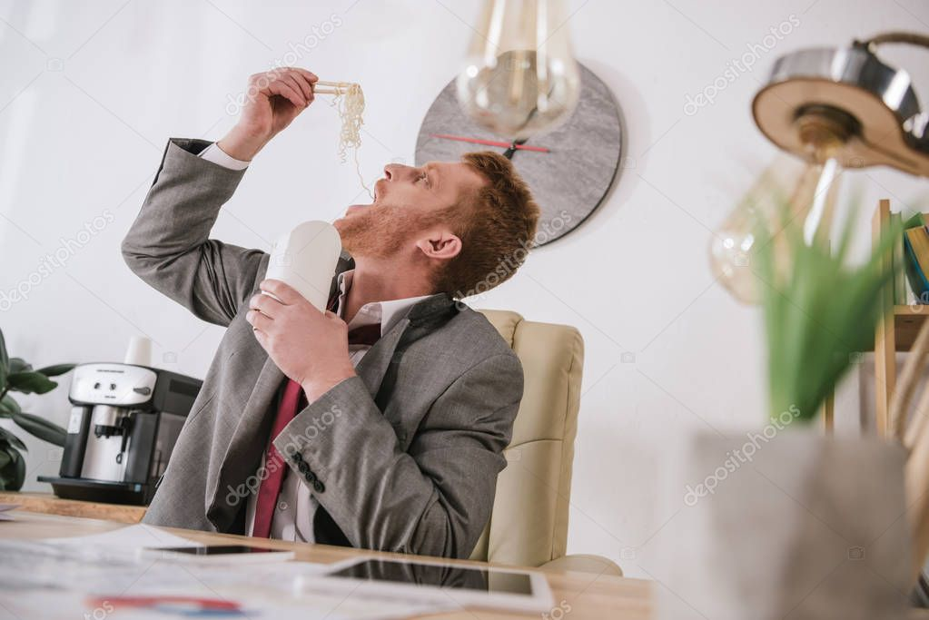 overworked young businessman eating take away noodles at workplace