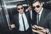 Leibwächter stoppen Paparazzi und Promis, die Gesicht mit Hand im Fahrstuhl verdecken