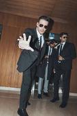 Leibwächter mit Sonnenbrille stoppt Paparazzi, wenn Promi aus Fahrstuhl geht