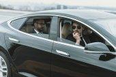 osobní strážce sedí v autě s podnikatelem a mluví o přenosné rádio