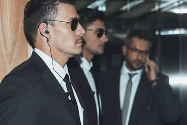 profile of bodyguards in sunglasses and businessman talking by smartphone