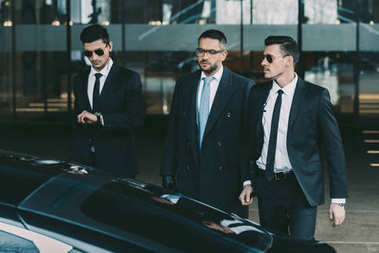 two bodyguards going with businessman to black car