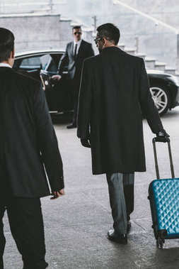 businessman going with blue travel bag to car