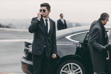 bodyguard talking by portable radio near businessman car