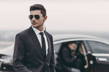 bodyguard reviewing territory while businessman going out from car