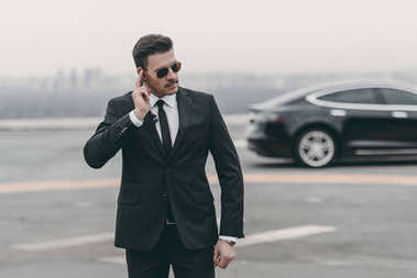 serious bodyguard listening message with security earpiece on helipad