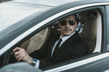 bodyguard sitting in car with businessman and looking away