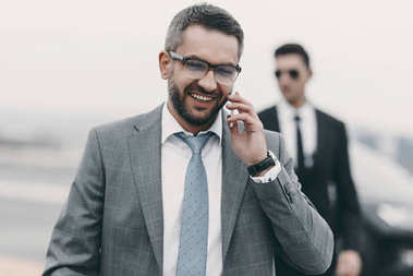 smiling businessman with bodyguard talking by smartphone