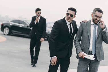 happy businessman walking with bodyguards and talking by smartphone