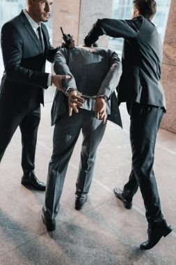 Cropped image of security guards arresting offender