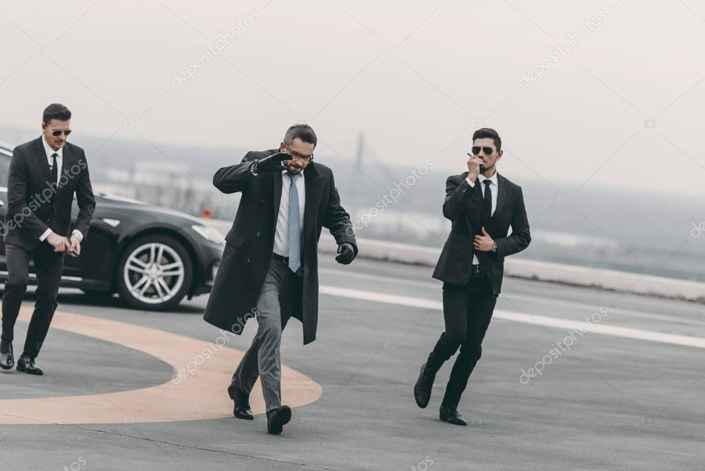 businessman covering his face with hand and walking with bodyguards