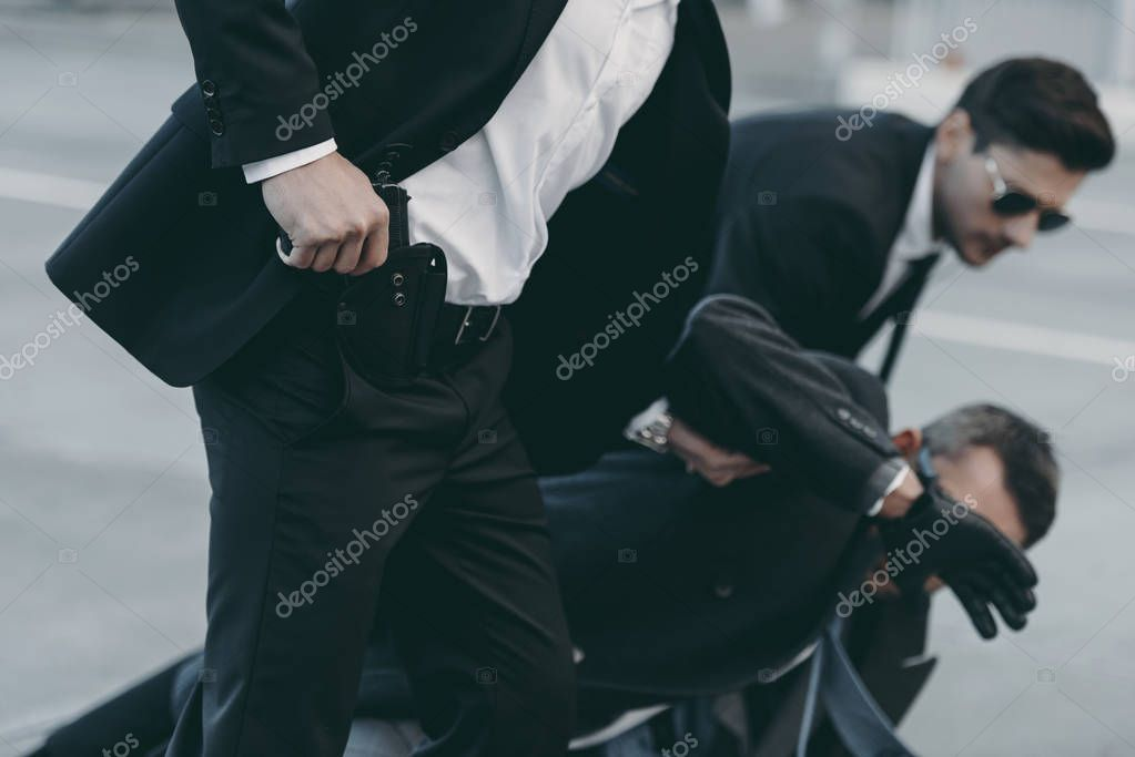 cropped image of bodyguards protecting falling businessman